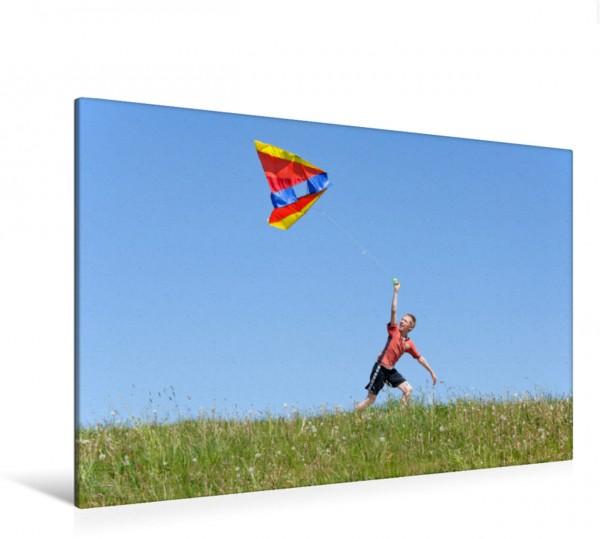 Wandbild Drachen steigen lassen Ein Junge lässt auf einer Wiese einen Drachen steigen. Ein Junge lässt auf einer Wiese einen Drachen steigen.